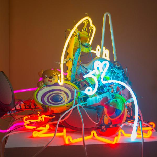 A jumbled heap of many colors of lit neon with plastic cords and wires and plastic toys including a brown dog, and two speakers are set atop a white platform in a white walled corner.