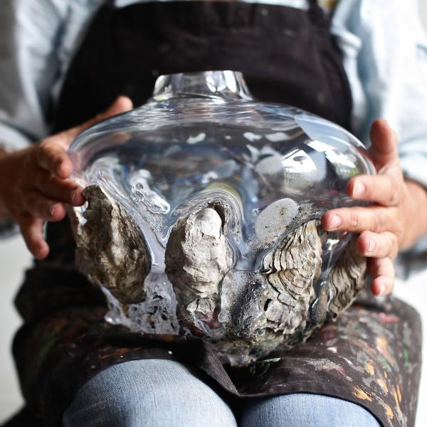 A light-skinned person holds a clear glass vessel on their lap. The vessel is embedded with rocks, seaweed, and oyster shells.