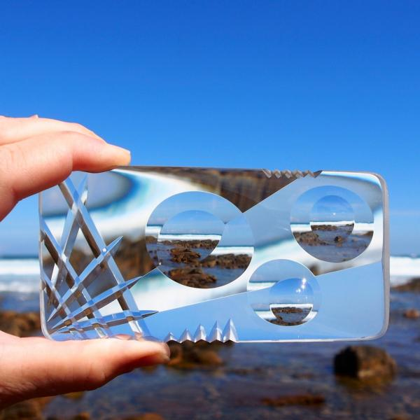 A man's hand holds a smartphone-size piece of cut glass as if taking a photo of a rocky beach. The image of the beach is distorted through the cut glass.