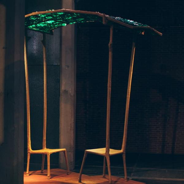 Two chairs face each other, the backs approximately 9-feet high. The backs support a canopy of green glass, made from beer bottles, over the chairs.