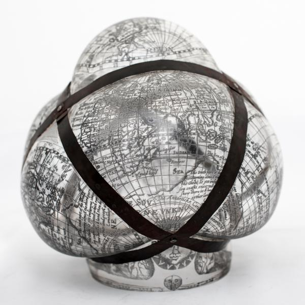 A clear blown glass globe looks like it is being squeezed by a lattice of black bands wrapped around it.