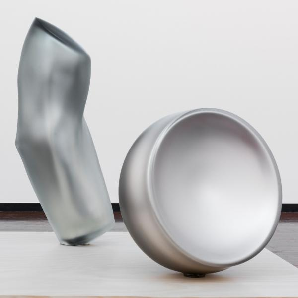 An installation of three blown glass forms in a gallery. In the background, a mirrored silver slightly bent cylinder sits stop a matte black pedestal. In the foreground, two matte silvered forms—one a similar slightly bent cylinder, the other a half-sphere—sit atop a light wood table.