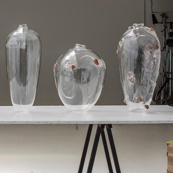 Five clear glass vases sit on a table. Embedded in each are rocks, broken bricks, or broken window glass causing each vase to crack and disintegrate.