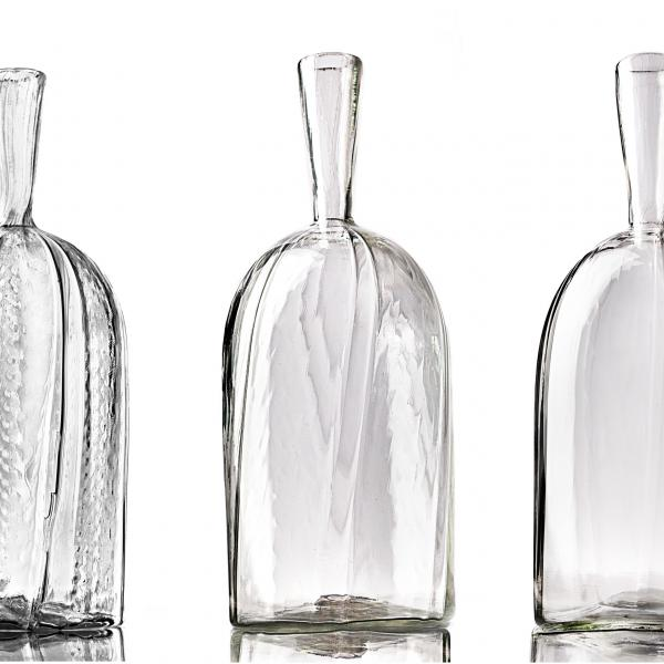Three clear glass bottles with narrow necks. Each bottle has a subtle vertical striped pattern from more complex (far left) to least complex (far right).