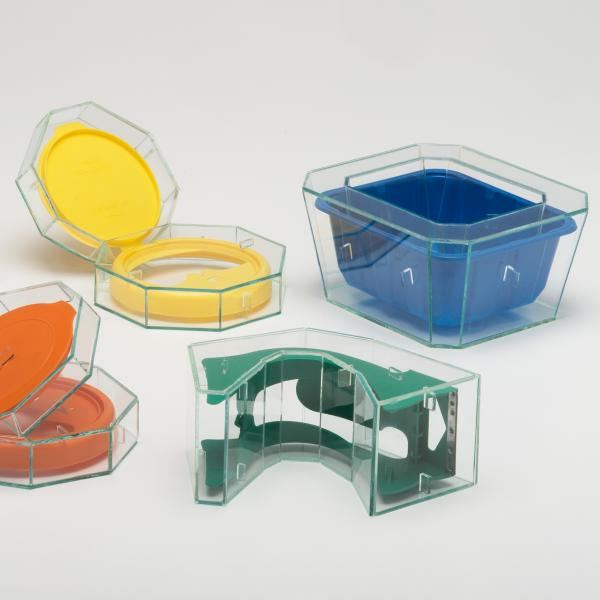 Group of five small plastic parts of everyday objects encased in angular flat glass cases. The items include shipping tape dispensers.
