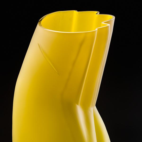 Yellow glass vessel, with a slash near the top, that suggests the form and folds of a woman's dress.