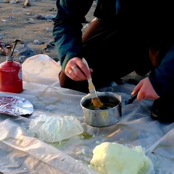 A woman in a teal Arcteryx jacket and winter hat sits on a sandy and rocky beach near water with mountains in the distance. She's holding a paintbrush and pot of melted wax and has chunks of wax sitting in front of her.