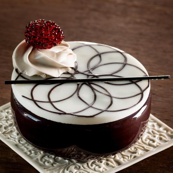 Rendered in glass, a round chocolate cheesecake with white icing, and a swirl of whipped cream with a raspberry on top. The cake sits on a cream-colored square plate.