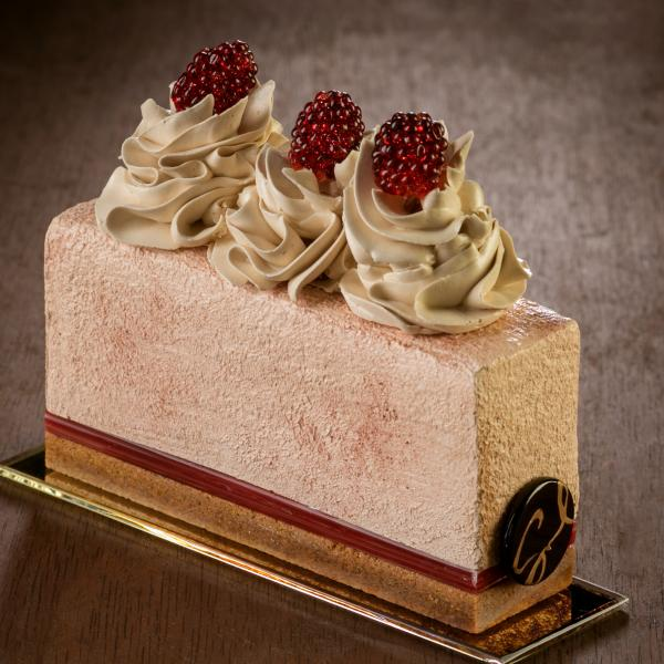 Rendered in glass, a rectangular piece of cheesecake with graham cracker crust is topped with three swirls of whipped cream each topped with a raspberry. The cake sits on a gold rectangular plate.