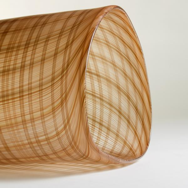 An oblong blown glass vessel with stripes of brown, gold, and orange that suggest the texture of a woven basket.