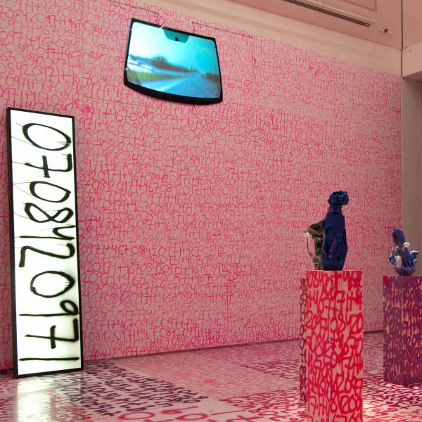 Pink graffiti numbers cover the walls and floor of a room. A large white panel with black numbers leans against one wall. A monitor at the top of the wall shows the view from a rearview mirror. A pink neon yin/yang shape hangs on the opposite wall. Six pedestals, also covered in graffiti, sit in the center of the room each topped with a glass sculpture.