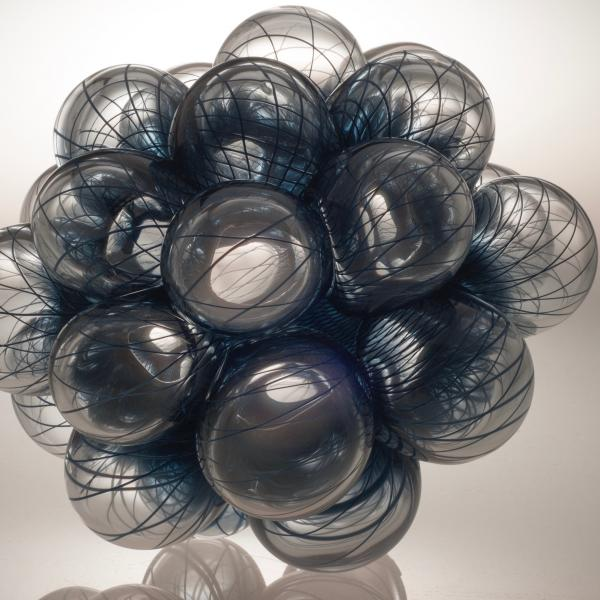A bunch of clear blown glass bubbles each decorated with intersecting and overlapping dark blue lines.