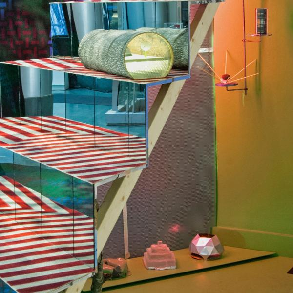 A mixed media installation that features a mirrored staircase with bold colored carpet on the run of the stair and another print of carpet on the wall behind. Lime green light covers the entire installation.