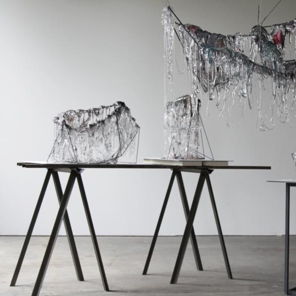 Chains, wires, and metal frames hanging from a ceiling are covered with thick drips of clear and gray glass. Metal armatures on tables are also covered in strings and drips of gray and clear glass.
