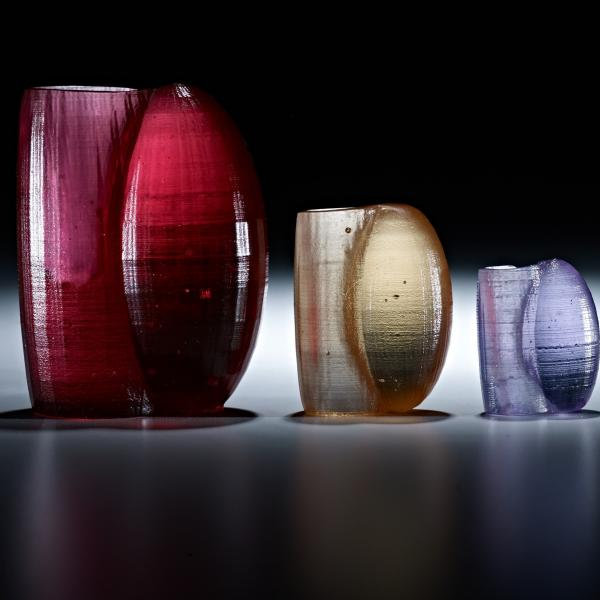 Six vessels arranged in order from largest to smallest, each in a different color—red, tan, purple, green, pink, black. Each has an oval shape protruding from its side where a handle should be.