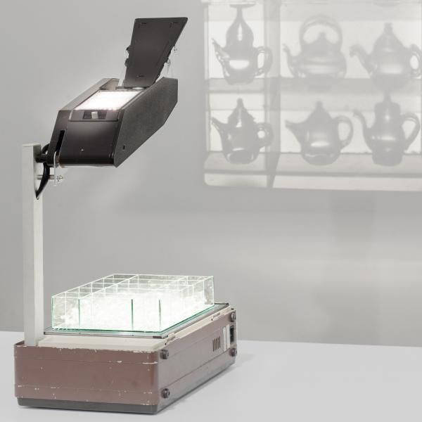 An overhead projector sits on a white table. On the bed of the projector is a clear display case holding 20 small glass teapots which are projected onto the white wall in front of the projector.