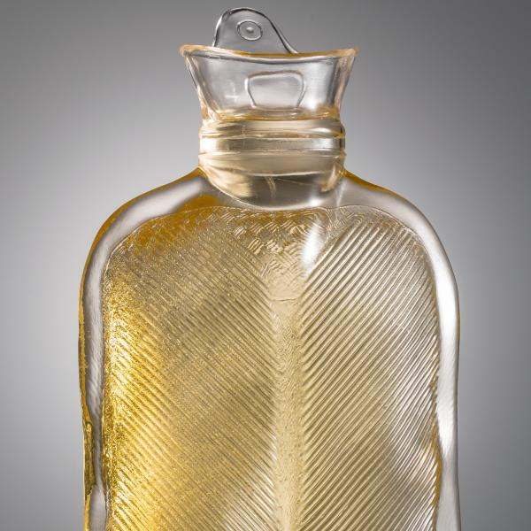 A translucent gold glass hot-water bottle stands upright on two feet that are wearing what look like work boots.