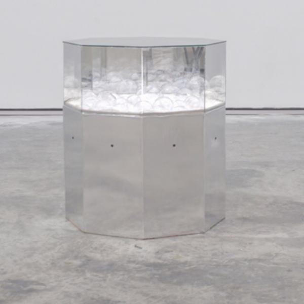 A group of clear glass bubbles encased in an octagonal mirrored pedestal in a room with concrete floors and a white wall. The right half of the image is a detail of the flameworked clear glass egg-shaped bubbles.
