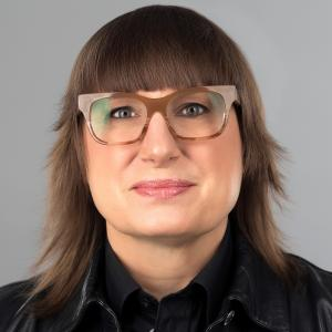 Woman with medium-length brown hair, blunt bangs, brown glasses, black shirt and black leather jacket.