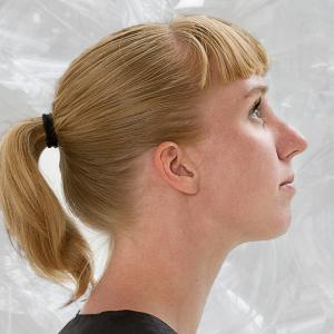 Woman with medium-length blonde hair pulled into a pony-tail and blunt bangs stands in profile wearing a black shirt.