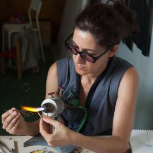 Woman sits at a work table working with a flameworking torch. She wears sunglasses and her dark hair is pulled back into a ponytail.