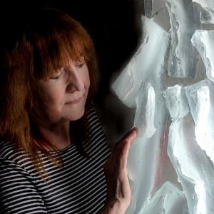 Middle-aged woman with medium-length red hair wearing a black and white horizontally striped shirt. She stands next to a large glass sculpture.