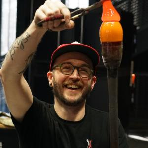 Man with short brown hair and beard wearing a red baseball cap and black t-shirt. He stands in a hotshop grasping a gather of glass with diamond shears that is resting on another gather attached to a punty.