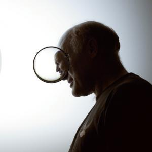 An adult man with short hair stands in profile. A glass lens in the foreground distorts his profile while a large white disk fills the background.